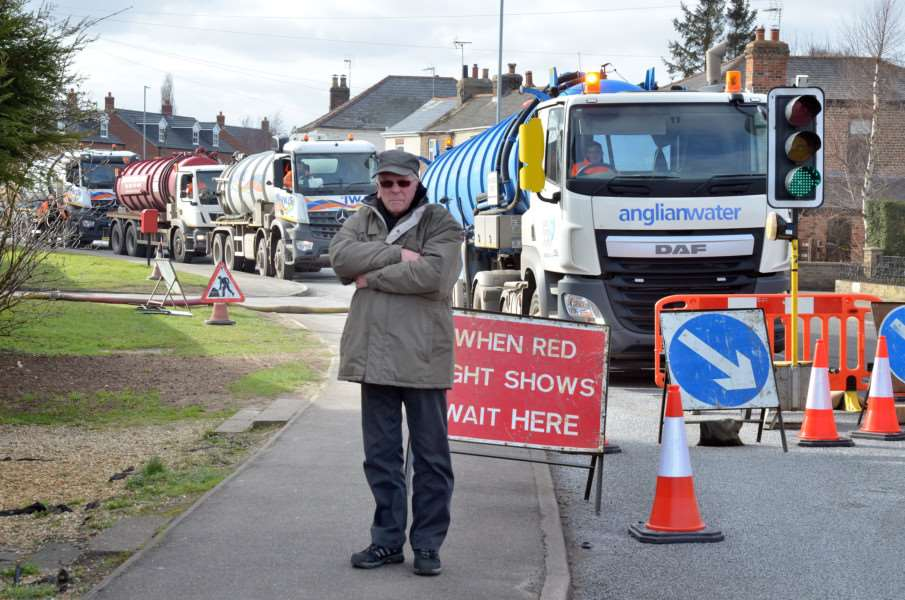 Resident Paul Ingham with sewage tankers in London Road. Photo (TIM WILSON): SG200318-106TW