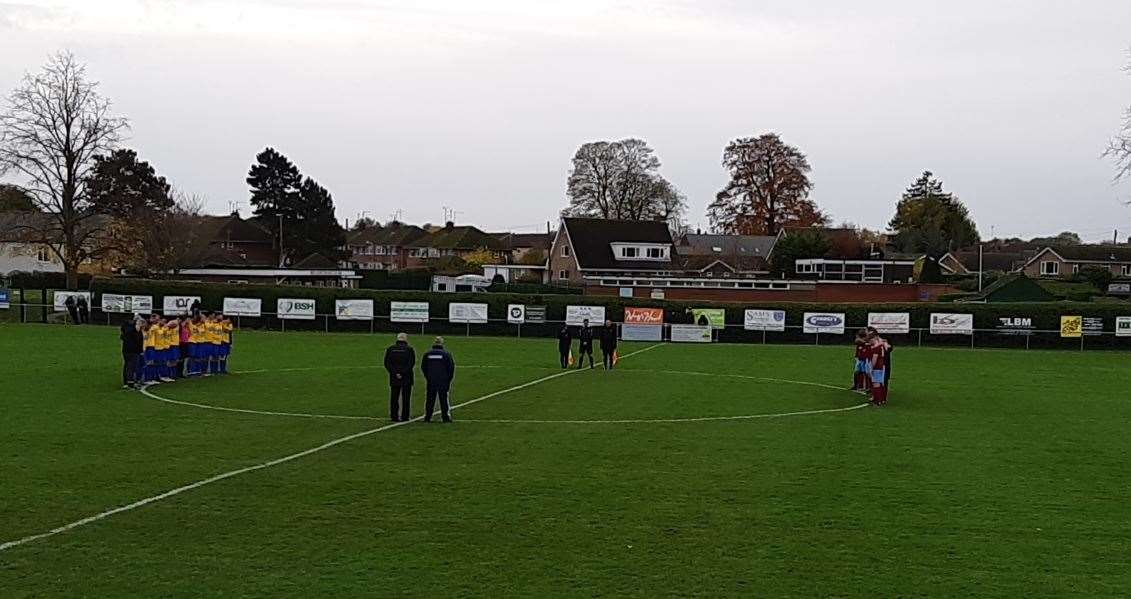 Bourne Town and Bugbrooke St Michaels players observe a minute's silence on the eve of Remembrance Sunday.