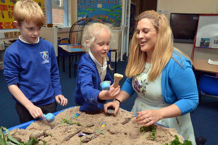 Pupils show Mrs Walker their work in the sand pit at Weston St Mary Primary School. Photo by Tim Wilson. SG-210918-080TW