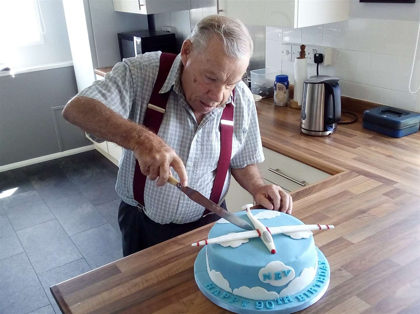 Neville Robinson cuts his glider themed 90th birthday cake