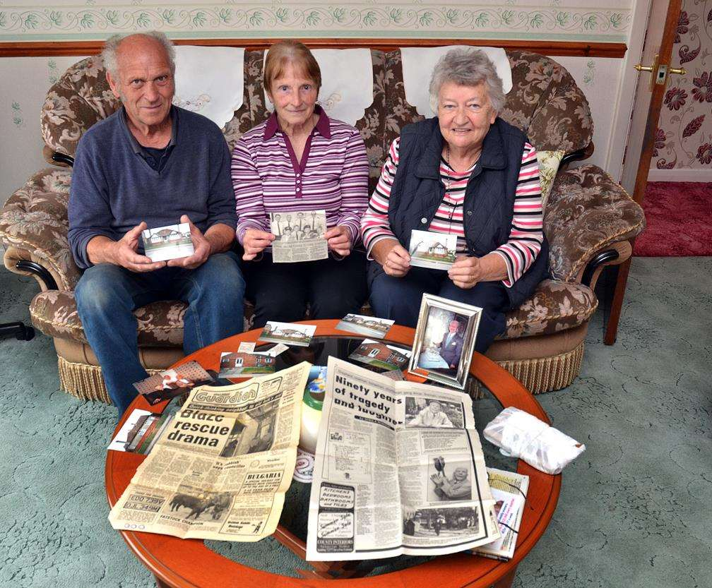 Brian Dobney, Ann Dobney and Jane Stanley with newspaper cuttings about Ernie and photographs.