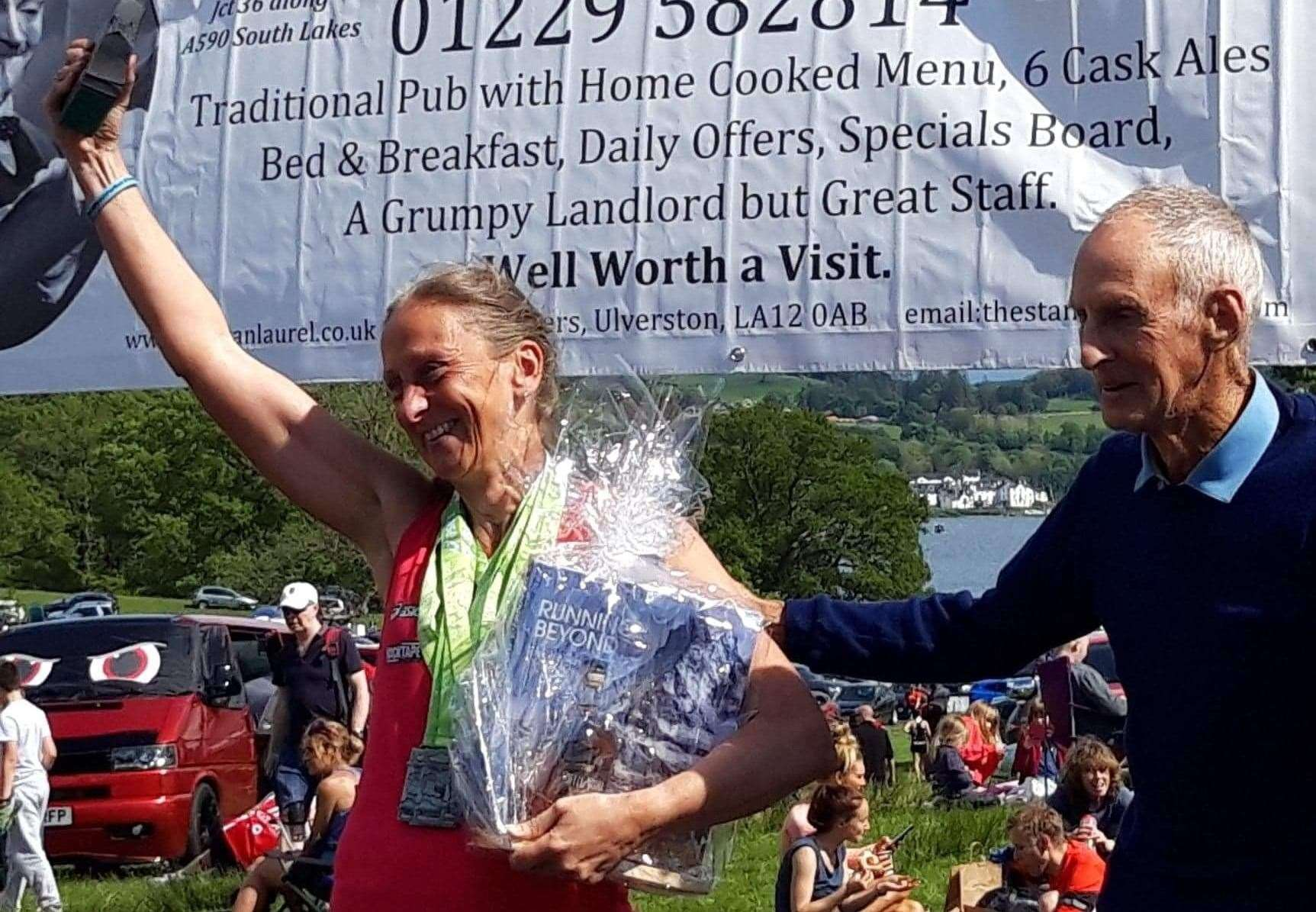 Diane Morris completes the Brathay 10 in 10, again, with legendary fell runner Joss Naylor MBE presenting her with a shield and flowers.Photo supplied.