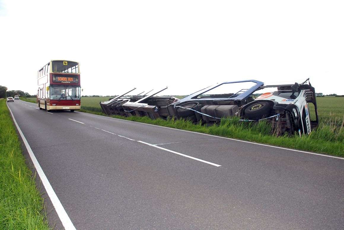 A school bus drives past a transporter that was carrying vehicles to a showroom in Whaplode Drove before it came off the B1166 Hulls Drove, near Shepeau Stow.Photo by Tim Wilson.SG-200619-106TW