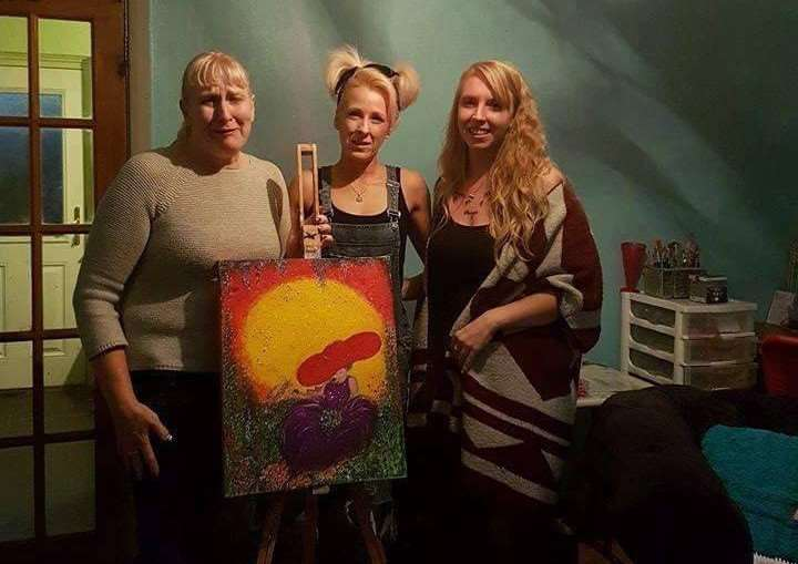 Zoemarie Sheldon (centre) presents the finished painting.