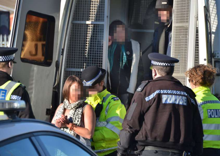 Three of the four people arrested being placed in a police van. SG2811117-104TW