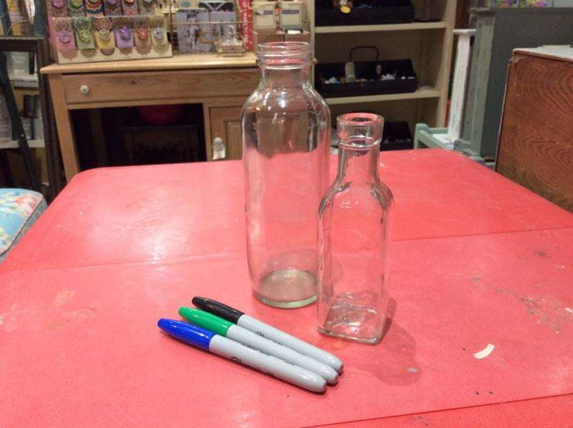 To start making your vase choose a glass bottle (or jar), some permanent markers, and get your creative head on!