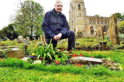 Library picture: the Rev Ian Walters beside the grave at Quadring. Photo (TIM WILSON): SG270418-101TW (2039500)