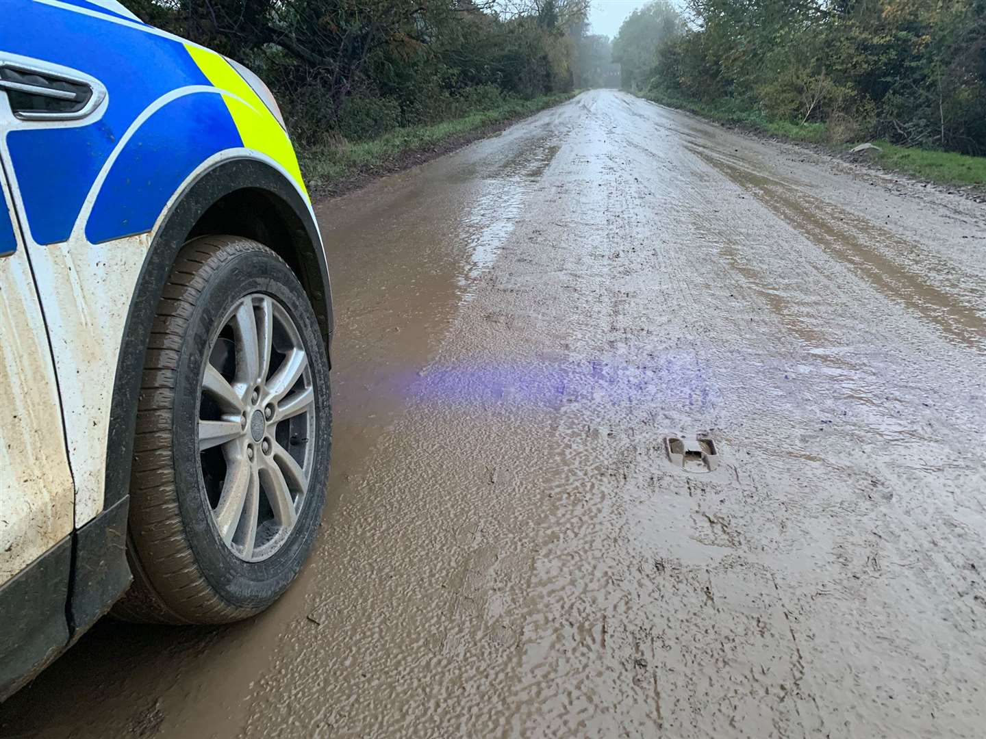 Police are at the scene of a muddy road.