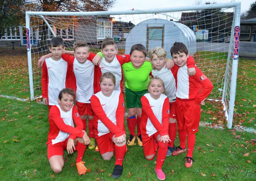 St Paul's young footballers celebrate the arrival of their new goals. SG221117-155TW