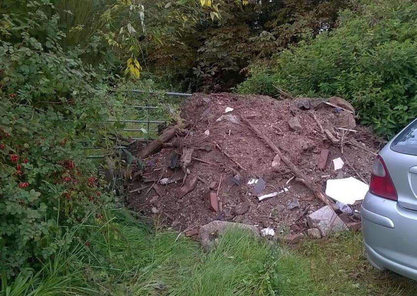 Tonnes of fly-tipped earth and rubble block the entrance to Angela's land.