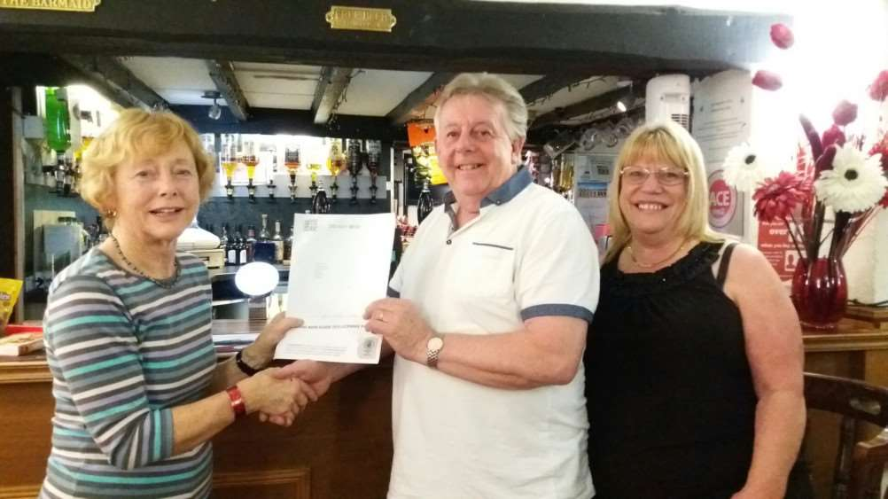 Drayman's Arms landlord Tony Branch and his wife Mary receive their notice of inclusion in the 2018 Good Beer Guide from Fenland CAMRA committee member Heather Girdlestone.