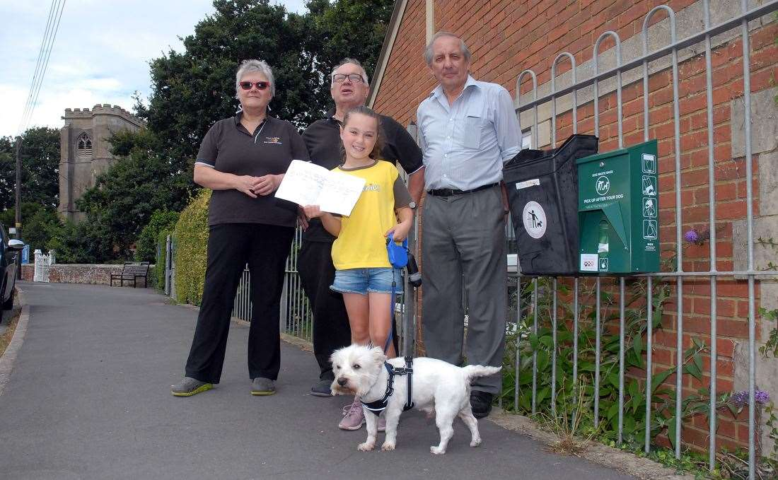 TAKING ACTION: Lola McAllister and Freddie (front), Helen and Ray Vaitkevicieus, of Lincs Dog Training Made Easy, and Cowbit district council Anthony Casson next to one of the new dog bins and bag dispensers in Cowbit. Photo (TIM WILSON): SG-300719-002TW