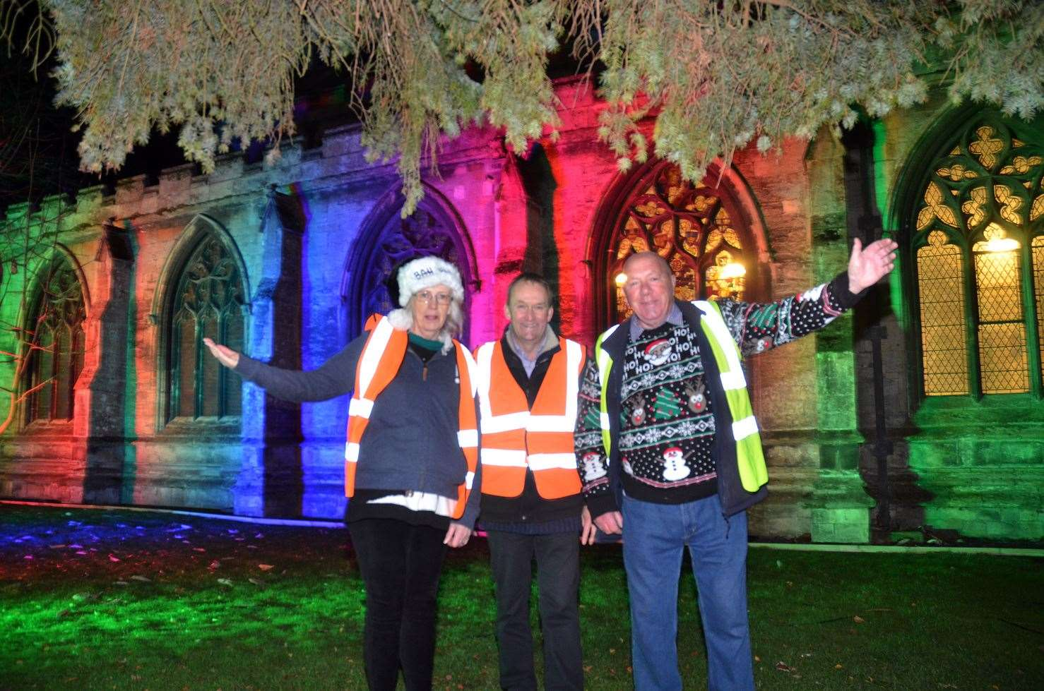 Organisers Jane Francis, Coun Nick Worth and Graham Rudkin at last year's Holbeach St Nicholas Christmas Fayre and Light Show outside the lit up All Saints Church.