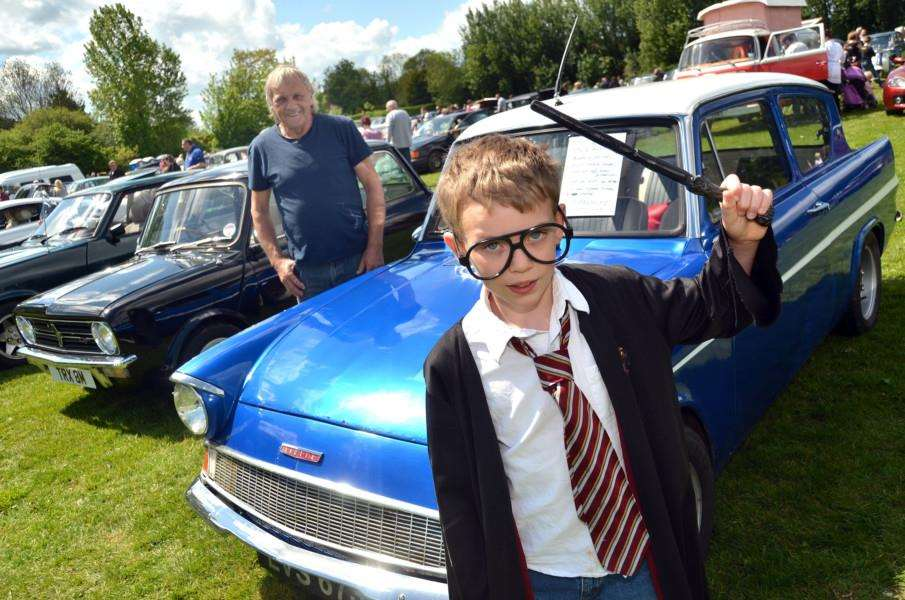 Louie Cross, as Harry Potter, conjures up a Ford Anglia, watched by car owner Michael Pack at last year's classic car show at Tydd St Mary. Photo: (TIM WILSON) SG140517-148TW