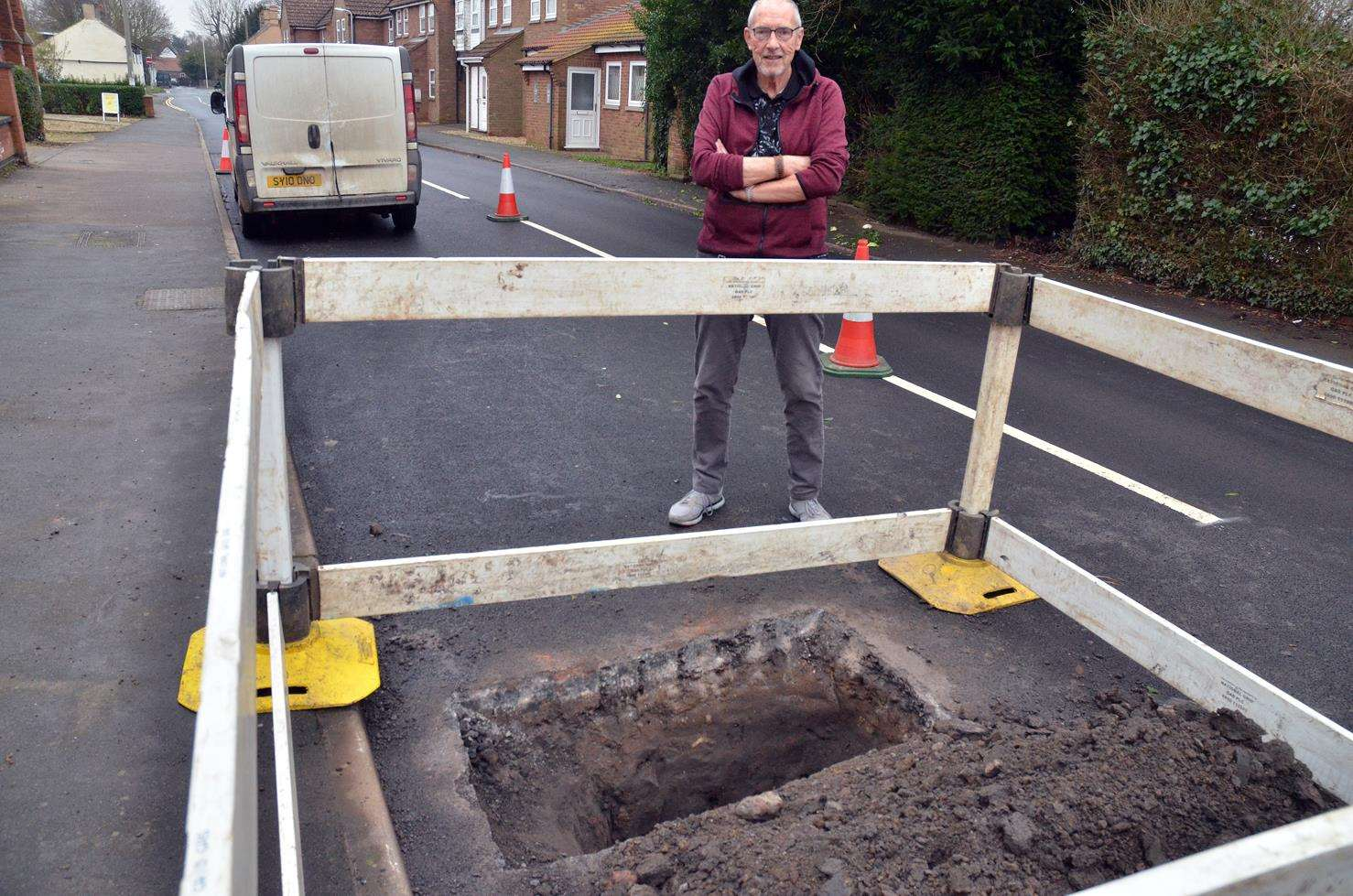 Resident Trevor Wardell beside a newly dug hole in Salem Street on Monday - road surfacing work finished on Friday. (050219-10)