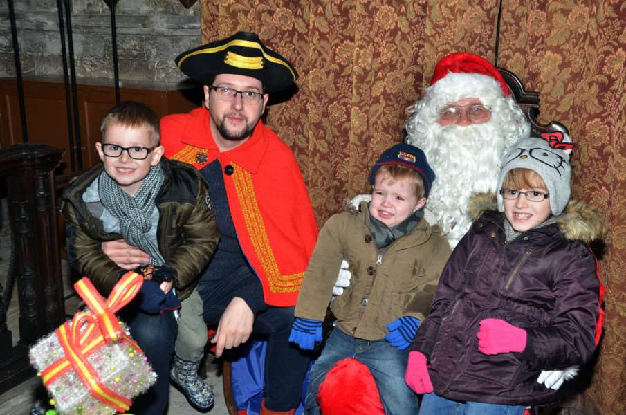 Dylan, Alicia Mai and George Chapman meet Santa Claus in the church with town crier and parish council chairman Charles Moore. SG101217-215TW