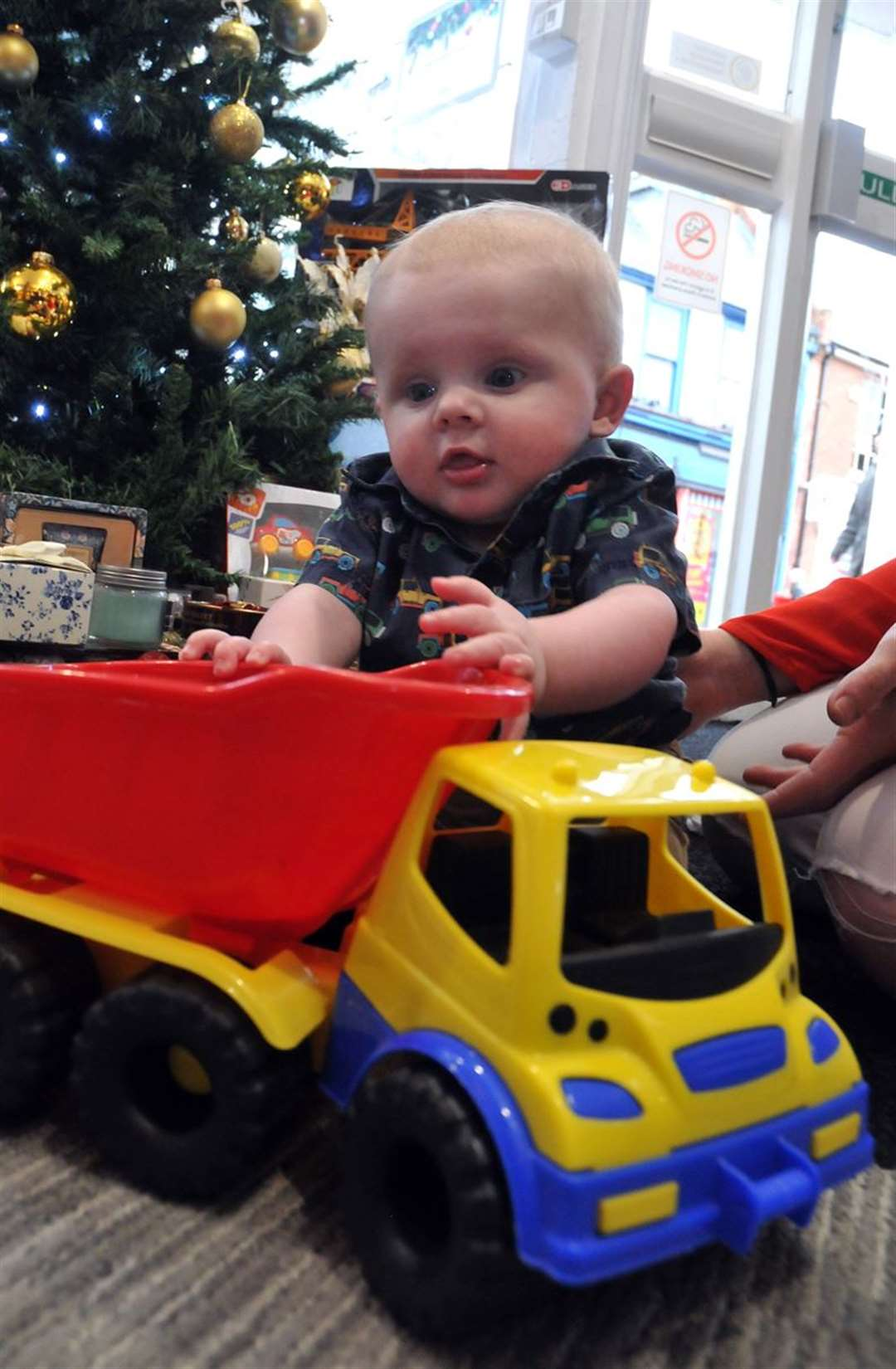 Baby James Gallagher tests out the toys under the Christmas tree at Co-op Travel