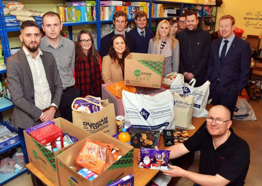 PROFESSIONAL KINDNESS: Members of Spalding Young Professionals present donations to Darren Fawcett of Agapecare Foodbank. Photo by Tim Wilson. SG071217-305TW.