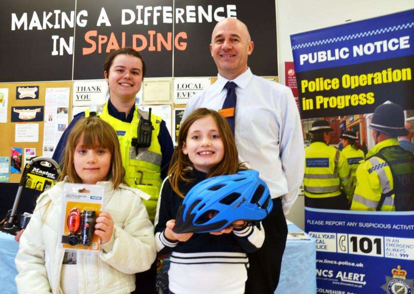 Youngsters Sarah and Bethan Jones (with) PCSO Jade Wallis and Sainsbury's store manager Dave Bassett who hosted a cycle security day run by Lincolnshire Police. Photo by Tim Wilson.''SG060418-105TW.