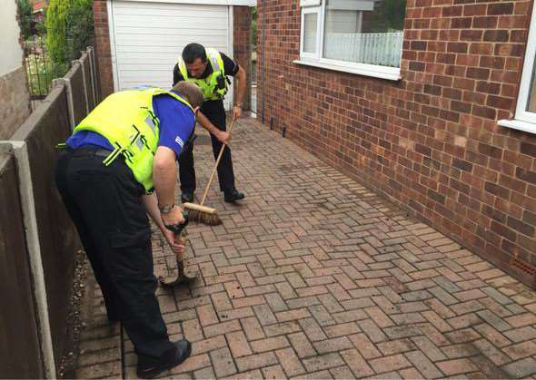 Police cleaning up the drive of an elderly person who was the victim of rogue contractors. Photo supplied.