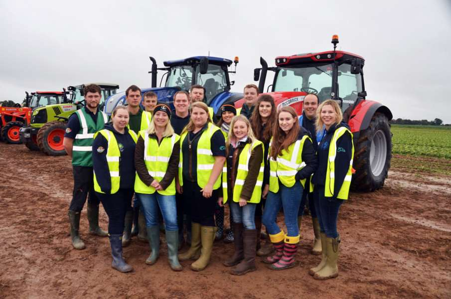 Spalding YFC members in front of two modern tractors.