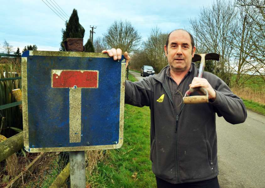 BIG SOCIETY: Dowsdale Bank villager Angelo Convertino and no 'No Through Road ' sign he has put back up near his home.''Photo by Tim Wilson. SG290318-206TW.