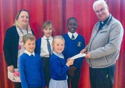 Pupils from Pinchbeck east Primary School present the proceeds of their bake sale to Rev David Sweeting.