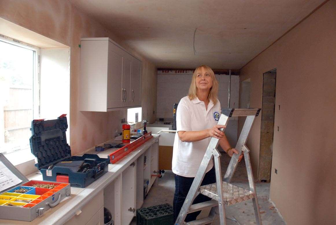 Volunteer Sharon Spikings checks plaster work in the new kitchen area prior to painting.
