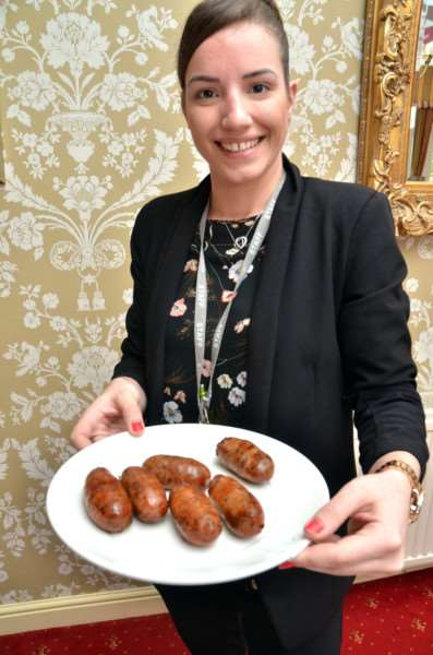 Summer Robinson from the Boston College organising team takes abnother plate of sausages to the judges.