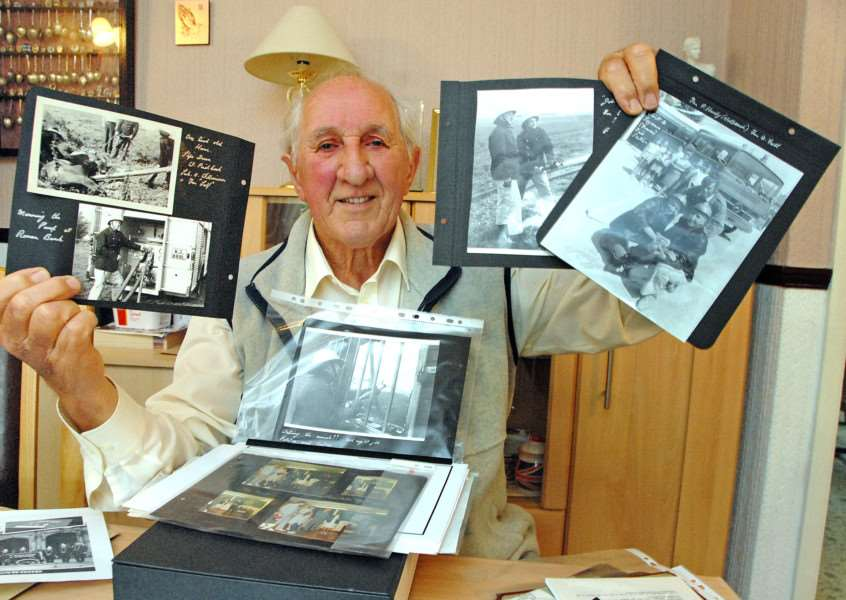 Dennis pictured in 2013 with photographs from his fire service days. SG100913-152TW