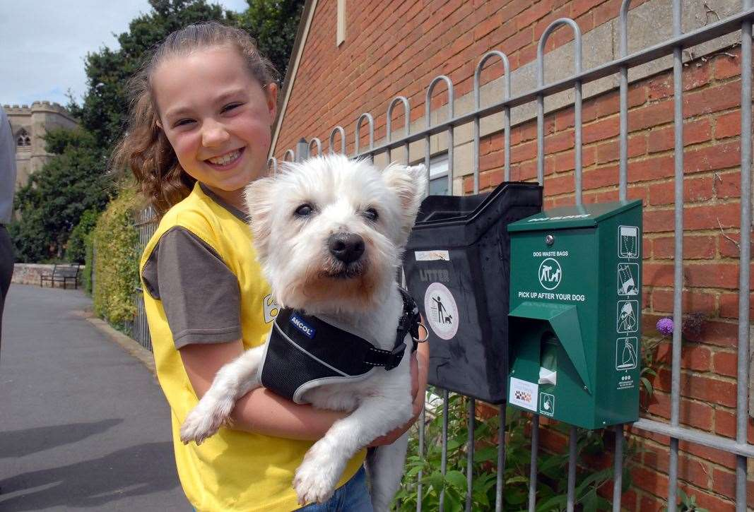 MAKE CHANGE: Lola McAllister, with West Highland Terrier Freddie, next to one of the new dog bins and bag dispensers in Cowbit. Photo by Tim Wilson. SG-300719-006TW