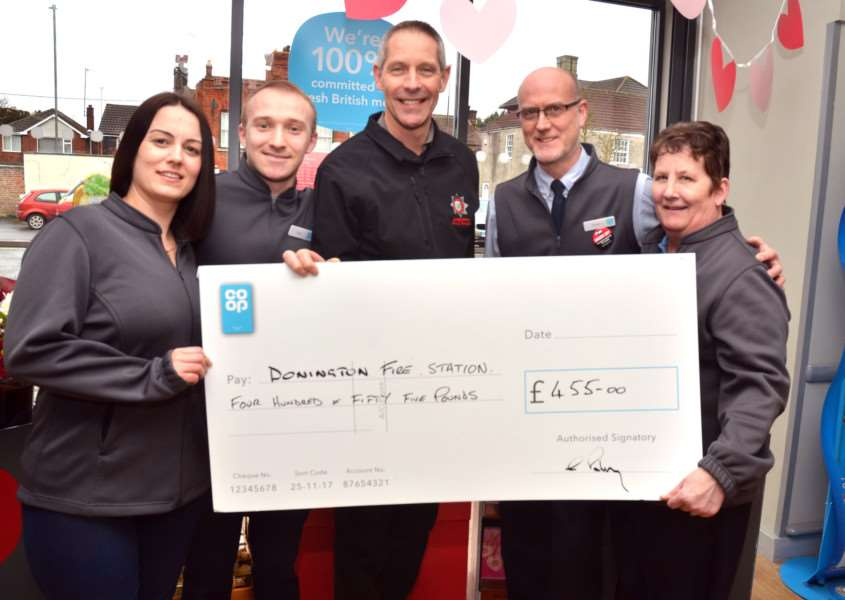 Firefighter John Scott (front), watch manager at Donington Fire Station, accepts a cheque for �455 raised at the village's Coop store from staff members Emma Minards, Dan Beasley, store manager Chris Pashley and baker Marion Kendall. Photo by Tim Wilson. SG130218-106TW.
