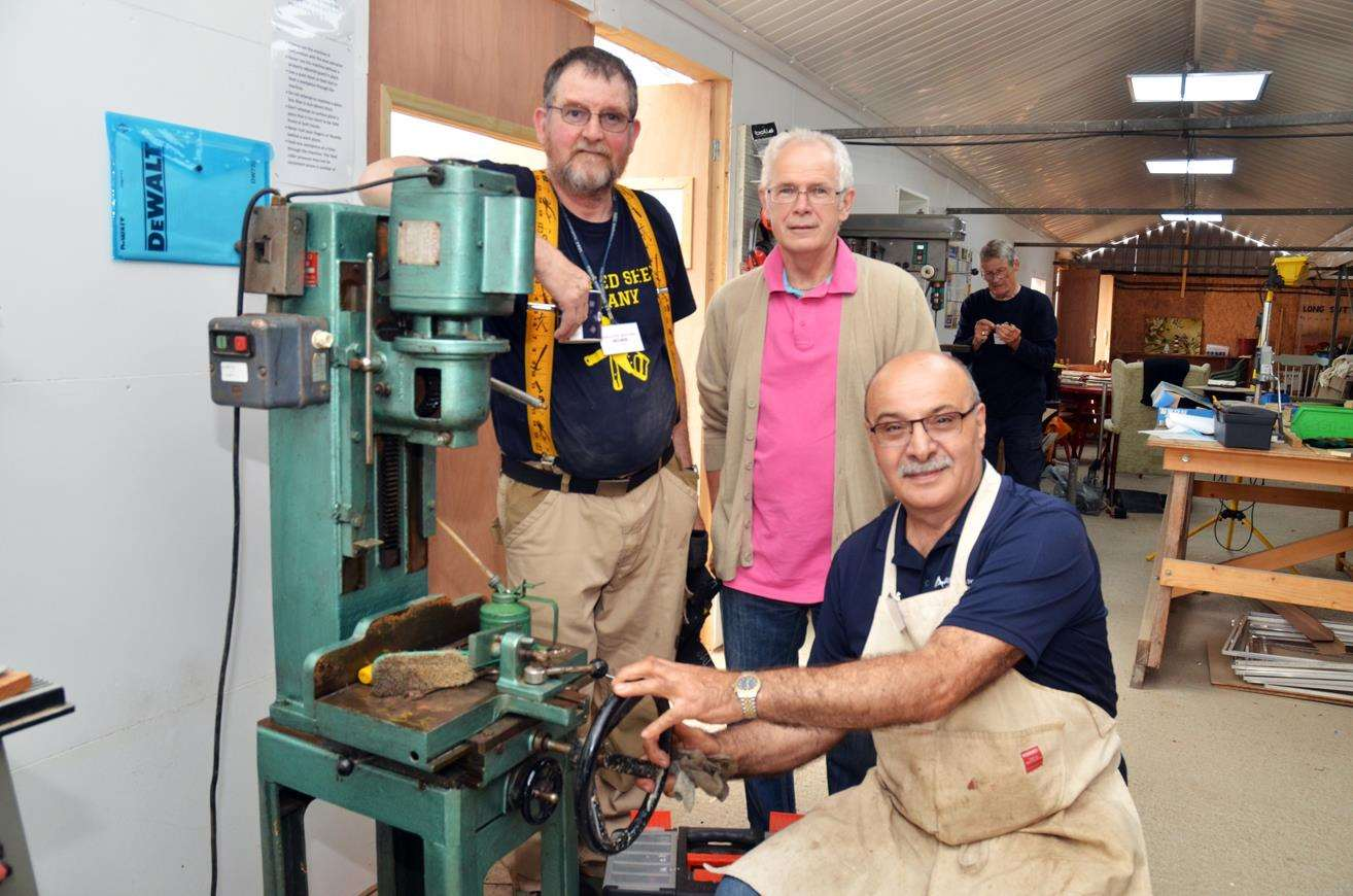 Restoring a mortiser, a specialist woodworking machine, are Dave 'Delboy' Wilson, David Stearn and Gabby Amodio.