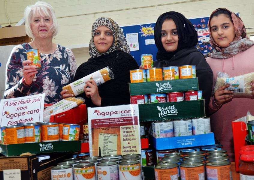 Irene Davies, co-ordinator of Agapecare Foodbank Spalding, accepts an Easter donation of groceries from Westlode Fisheries staff Fardous Ali, Taiyba Masaud and Sahra Ali. Photo by Tim Wilson. SG051218-119TW.