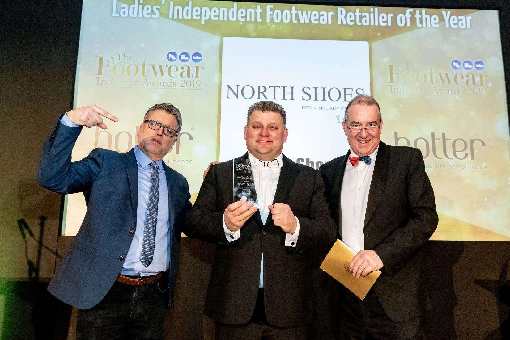 James North (centre) proudly displays the award for ladies independent retailer of the year alongside Footwear Industry Awards host Sean Collins (left) and Robert Perkins, chief operating officer of category sponsors, Hotter Shoes. (7306838)