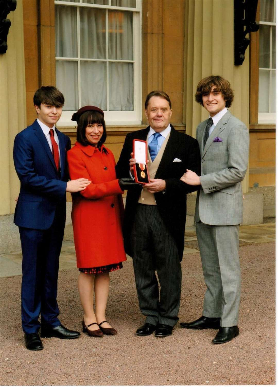 Sir John and Lady Hayes, with sons Edward (left) and William, outside Buckingham Palace after his knighthood. Photo supplied. (7373294)
