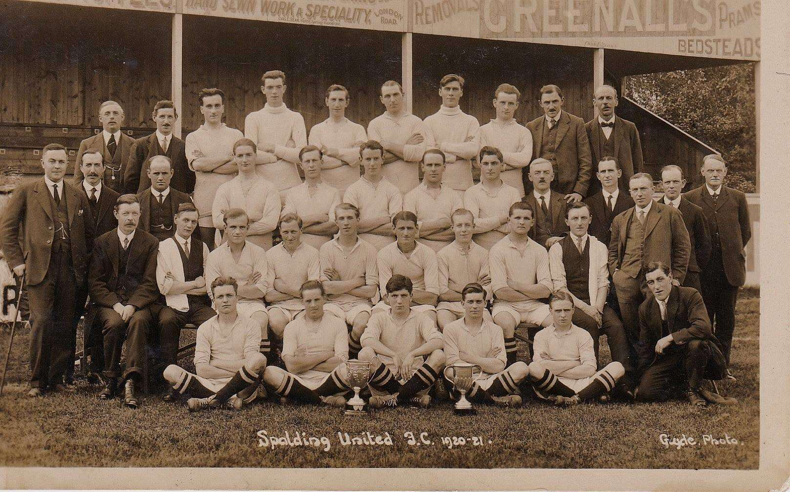 The 1920-21 team with the Peterborough Junior Trophy and The Victory Cup. The photograph was taken in front of the original grandstand at the Black Swan (Sir Halley Stewart Playing Field) by renowned Spalding photographer Gyde whose studio was situated in Gore Lane.
