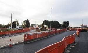 Kerbing being installed on the roundabout east of the A17 with a roller compacting surfacing material.