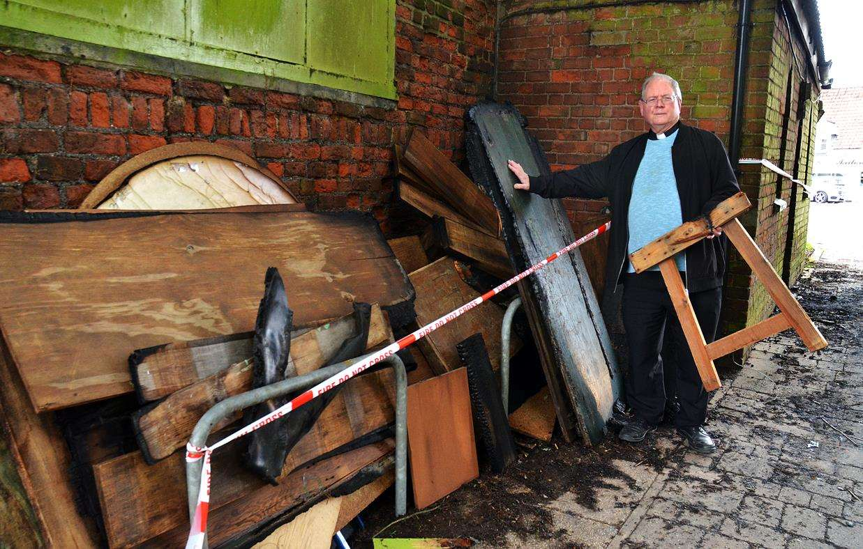 Father Jonathan Sibley surveys the wreckage after the midnight arson attack.