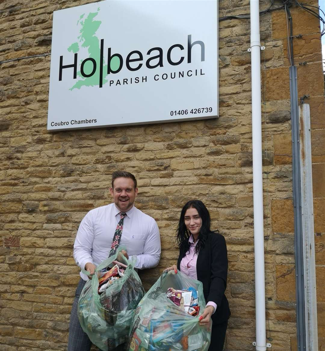 Parish clerk David Boyce and apprentice Brandi Rogan with some of the empty crisp packets dropped in at Holbeach Parish Council's offices in West End.Photo supplied.