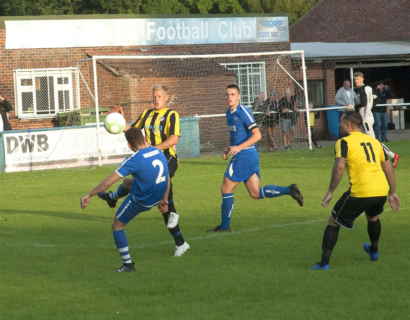 Holbeach United match winner Jack Smith (left) looks on as Michael Frew and Boston Town's Liam Harris clash.Photo by Michael Fysh.SG:060819-002MF