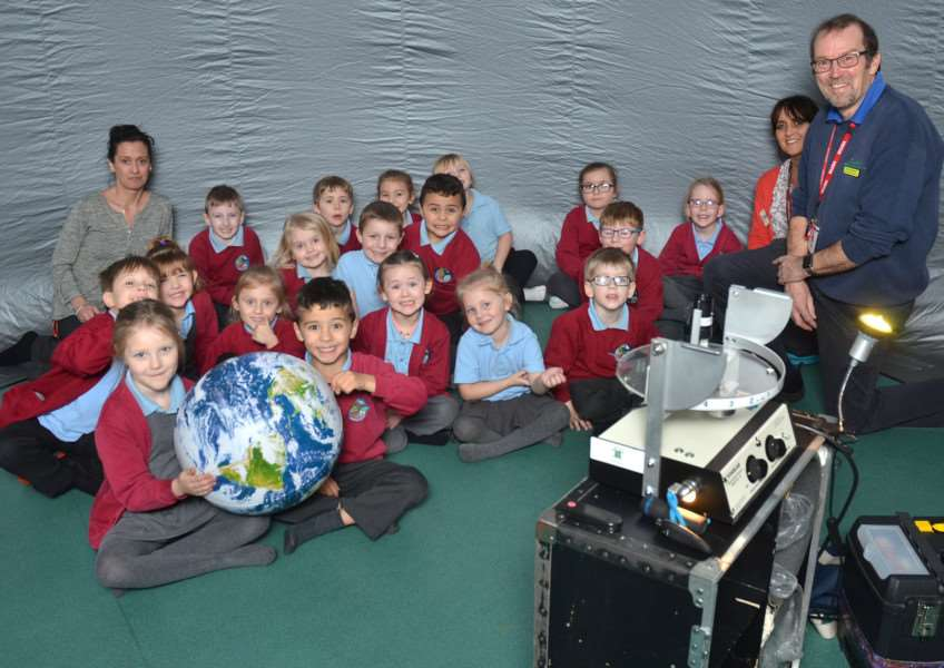 Children study the Earth and the stars in the Starlincs Mobile Planetarium. SG020218-101TW